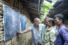 Farmers looks at sattelite images printout of Kanji village before CFR rights 2009 & after CFR rights in 2017  to see how their villages forest cover is improved after their practices after the village meeting in Sagai village.